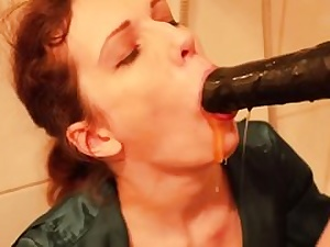 Horny mega-slut is getting face porked with a gigantic black strap on